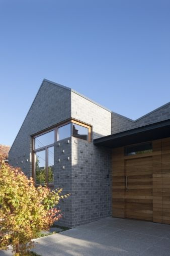 The home has a reinterpreted gable roofline and charcoal brick façade