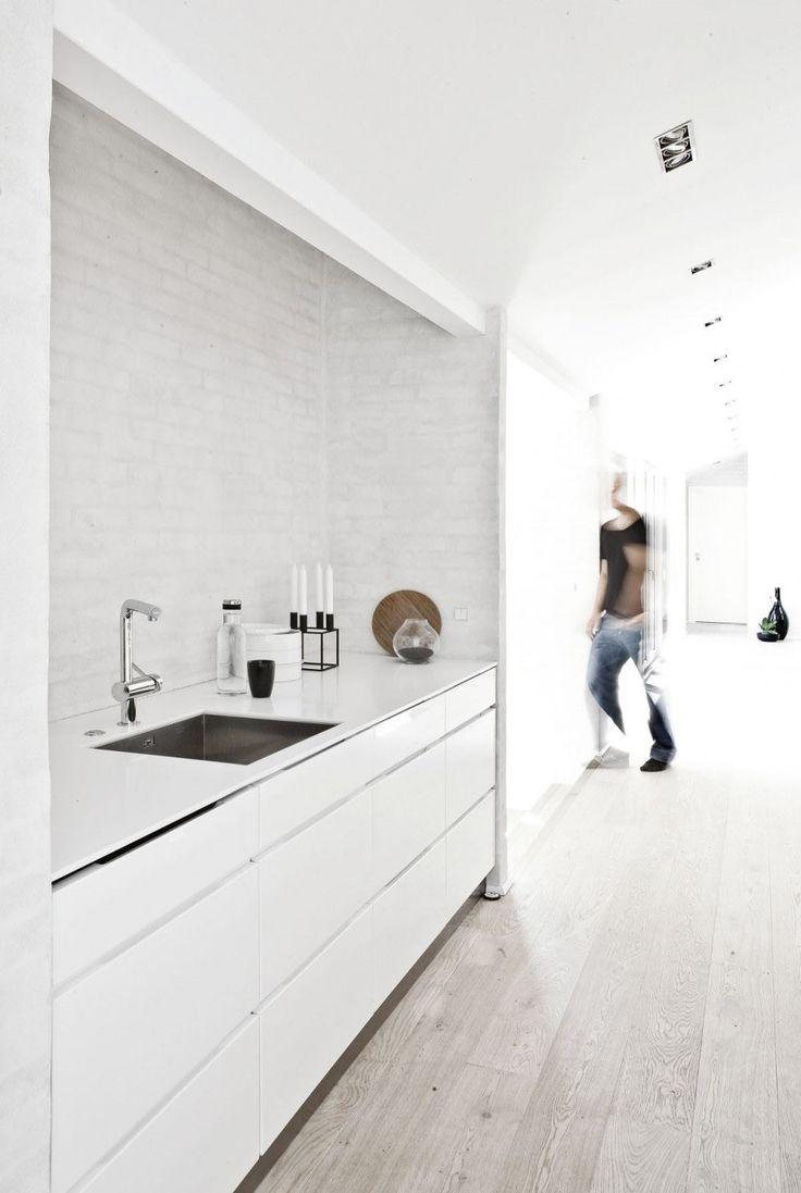 Minimalist kitchen design against wooden floorboards