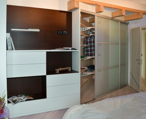 Walk-in closet with sliding doors in white satin glass milk. TV cabinet with drawers and shelves.  Cabinet back in wenge wood and drawers and shelves in white lacquered.