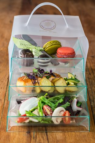 Lunch in elegant to-go bento boxes presented in a three-tier translucent container - Tastings