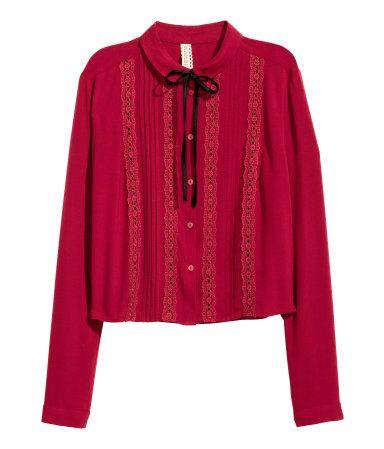 Donkerrood. Een blouse van viscose met een licht onregelmatige structuur. De blouse heeft ingezette biezen van opengewerkt kant en platte, ingestikte