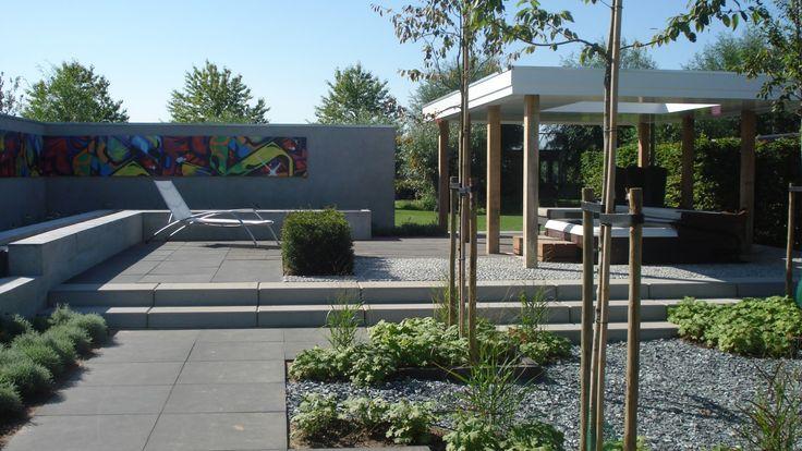 Een moderne tuin met loungegelegenheid en een jacuzzi. Kijk voor meer inspiratie op TuinTuin.nl.