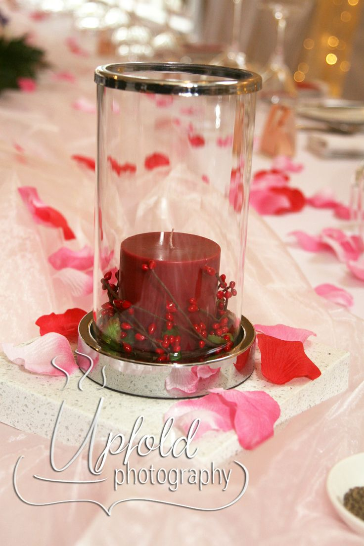 Red pillar candle in a cylindrical holder with berries ~ fresh and simple wedding table decor. Image by Upfold Photography, Auckland. Red wedding table decor ~ candles and berries ~ great for elegant Christmas decor ~