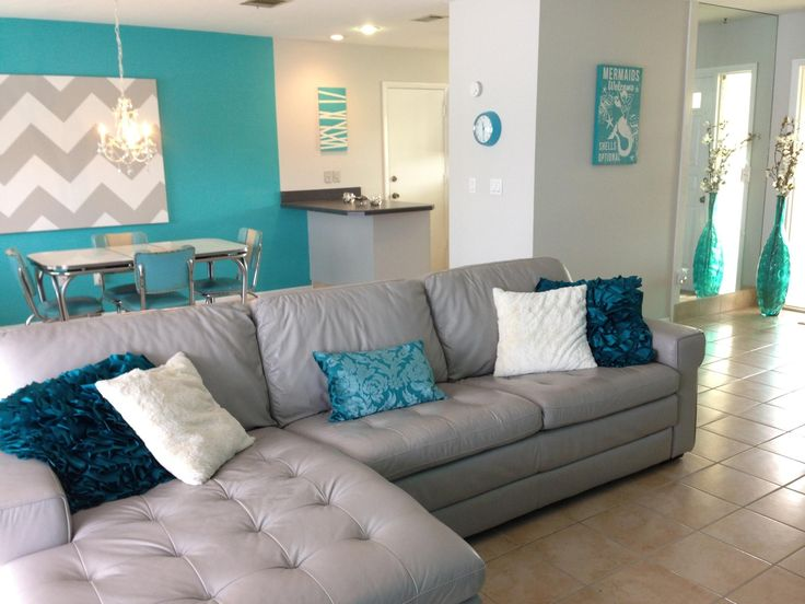 Florida home. Beach house. Leather couch. Homemade art. Tan and teal living room.