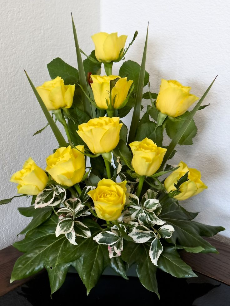 Roses with some Yucca leaves with fatsia leaves at the bottom of the arrangement