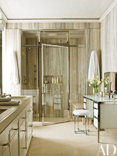 The walls in the master bath are clad in silver travertine from Walker Zanger; the '30s vanity stool by Samuel Marx is from Alan Moss | archdigest.com