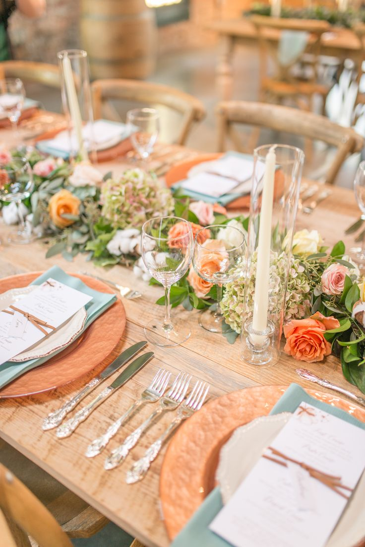 Table decor // wedding inspiration // sleeved candles // copper // chargers // dinner menu // teal napkins // pastel palette // pink // coral // yellow // farm tables // leather ribbon // hydrangea // wedding inspiration // wedding reception // reception dinner // table setting // flatware