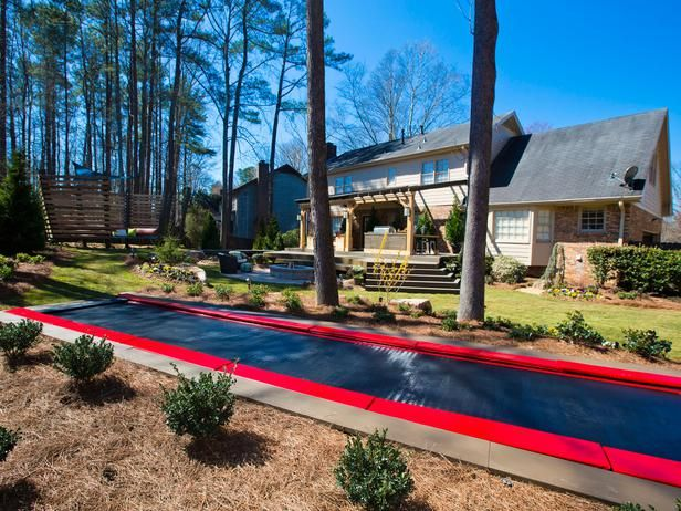 An outdoor tumble mat gives the homeowners' three daughters the perfect place to play and exercise in the backyard, while the parents can sit back on the nearby entertainment deck.
