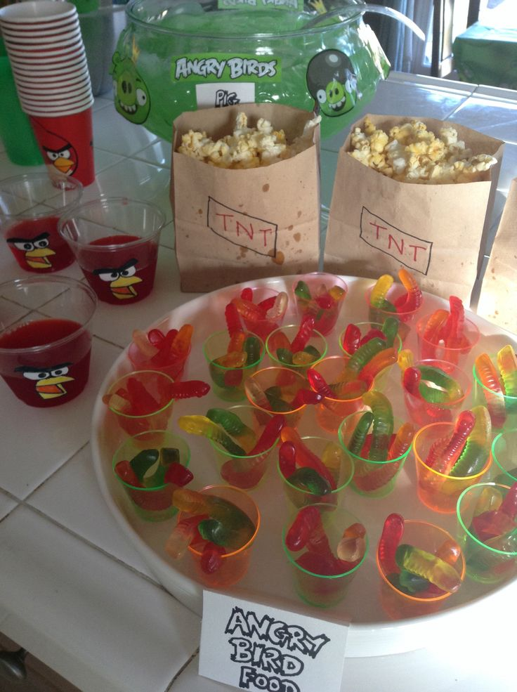 Angry Birds birthday party snacks: gummy worm bird food, TNT popcorn bags, Angry Birds jello cups