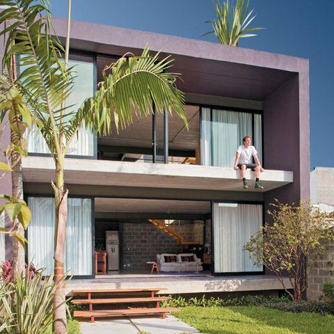 Placas de cimento de 1 x 1 m (Santorino Pisos) indicam o caminho da rua à casa. Os degraus são de itaúba, com as réguas fixadas sobre tubos metálicos pintados com a mesma cor do portão (Suvinil). Para contrastar com o tom do concreto, a fachada leva tinta acrílica fosca plum brown, da Sherwin-Williams.