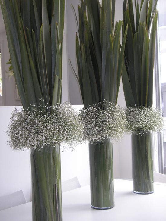 Baby's breath and flax leaves in glass vases: bold and unique centrepiece for your wedding dinner set-up.
