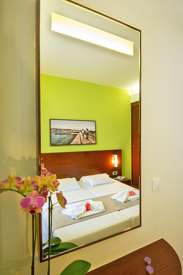 Oscar Suites & Village Studio room interior design. Double bed, night lamps, wall decor, wardrobe, private balcony