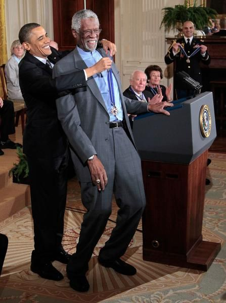 President Barack Obama reaches up to present a 2010 Presidential Medal of Freedom to basketball hall of fame member, former Boston Celtics coach and captain Bill Russell