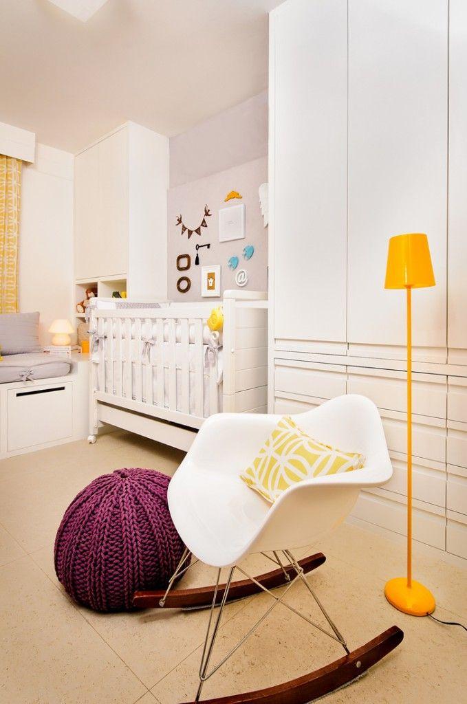 quarto de bebê super moderno, com linhas retas, marcenaria branca e detalhes em amarelo. Mapa mundi na parede, puff violeta e luminária de pé amarela. Almofadas coloridas e com grafismo. Projeto Renata Matos - cadeira de amamentar de balanço moderna