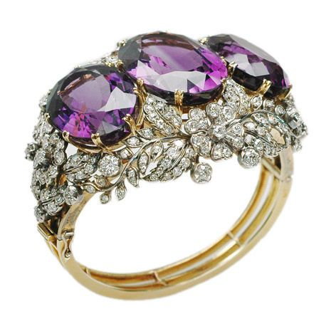 An antique amethyst and diamond bangle, designed as a series of three oval cut amethyst with a diamond set flower and leaf open surround, on a hinged band mounted in silver and gold, circa 1880.