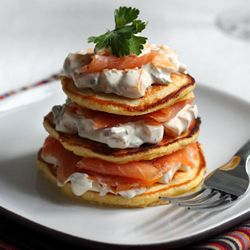 Smoked salmon and mango-jalapeño cream on cornmeal blinis. Adapted from Bobby Flay.