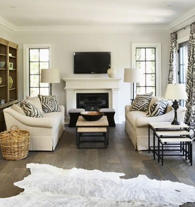 Neutral Living Room, Tv Above Fireplace, Dark Floors, White Animal Rug,  Furniture Arrangement
