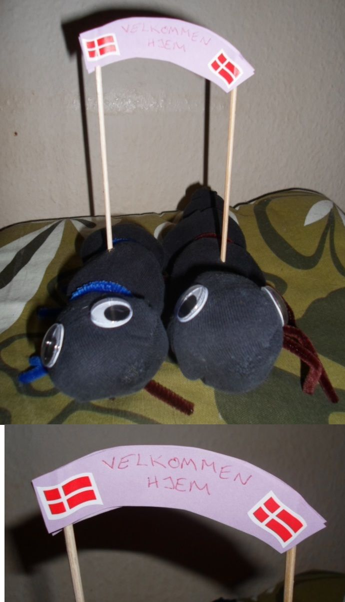 First I made a pair of socks into creatures. Then I made them carry a welcome home sign. It's for my parents when they return home from vacation.