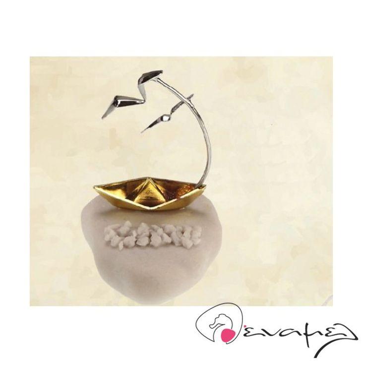 Μπομπονιέρες καραβάκι σε πετρούλα με δυο γλάρους να πετούν από πάνω. Μεταλλικό καραβάκι πάνω σε μεγάλη πέτρα και γύρω γύρω του μικρές πετρούλες.  Διαστάσεις: 9,5Χ6,5 εκ  Η τιμή αφορά έτοιμη δεμένη μπομπονιέρα με 5 κουφέτα αμυγδάλου Χατζηγιαννάκης.