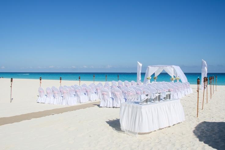 Stunning white beach wedding at Flamingo Cancun resort.