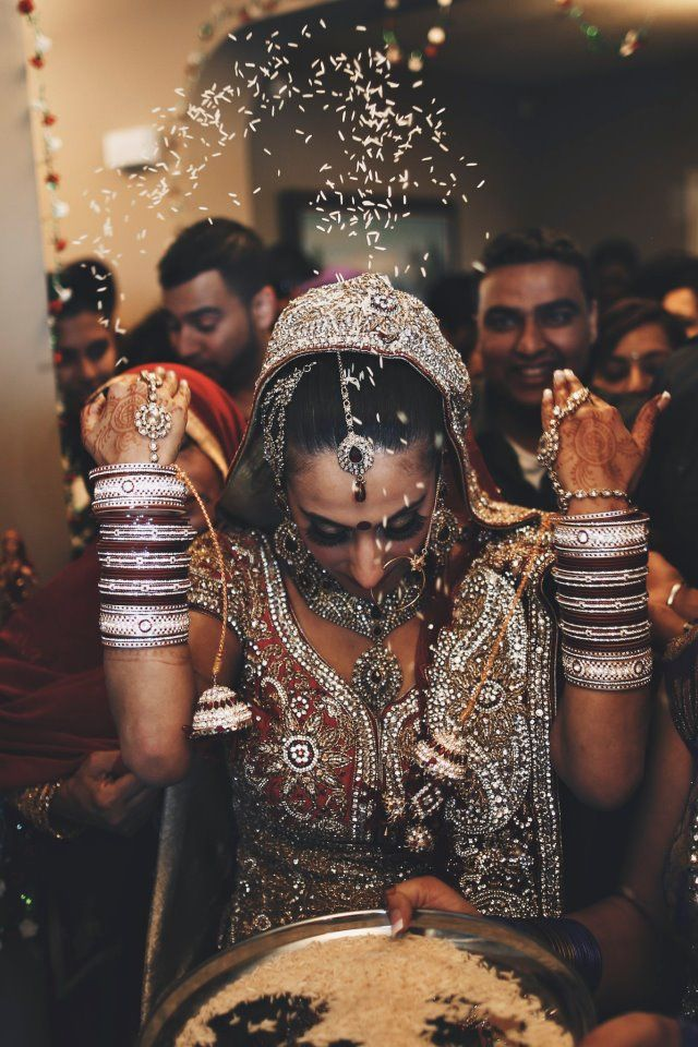 Indian bride at traditional ceremony. Throwing rice at weddings is a long standing tradition of prosperity (crops and harvest) and fertility (seeds of growth) and well wishes (good luck)