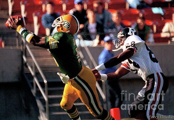 Edmonton Eskimos cornerback Stanley Blair #5 intercepts this pass intended for Ottawa Rough Riders wide receive Greg Lathan #88 in the endzone. Photograph taken during 1988.