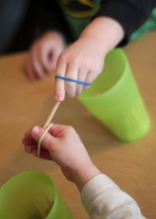 Passing objects with rubber bands for hand strength.  The object of the game is to fish the golf tees out of the cup and pass them to your partner to put into his or her cup with out dropping them.  Both children must keep the rubber band on their hands as shown.