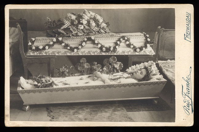 Goes to show how loved ones were laid out in burial attire, placed in casket, and viewed within the home until burial back in old days.
