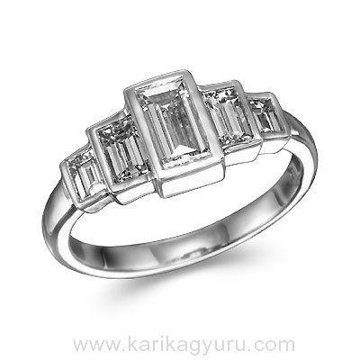 Modern öt köves eljegyzési gyűrű. 18K fehér arany foglalatban összesen 1,20ct súlyú, G/Si1 minősített emerald csiszolású gyémántokkal. A súlya kb. 3,20gr.