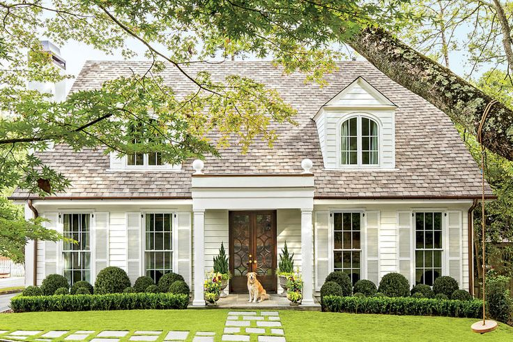 "Flattening the entrance's peaked roof and expanding it into a real porch was the key to creating a ""distinct entry for the home,"" says architect Corbett Scott. The new squared-off parapet, punctuated with 1-foot-tall finials, adds drama and depth to the exterior. French doors with a fresh Chippendale spin complement the Colonial home's English roots."