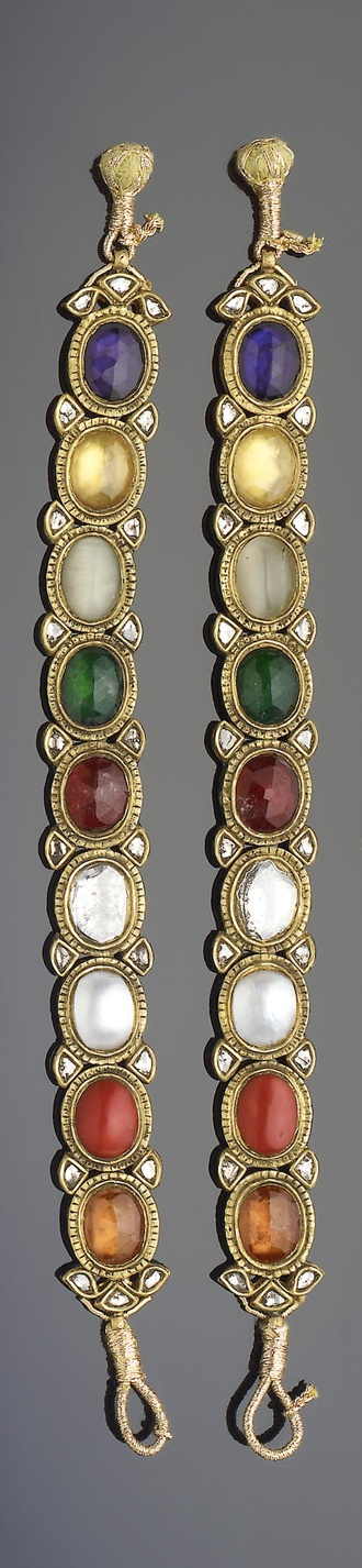 A pair of Indian gem-set enamelled gold Navratna Bracelets   each comprising nine interlinking oval elements set in gold, verso with floral enamel decoration   each 18.5 cm. long