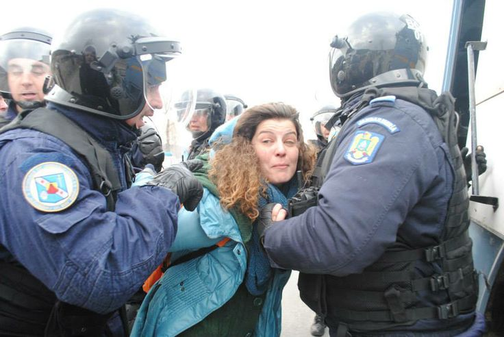 """Riot Police beating woman anti-fracking protester in Pungesti, Romania! Chevron is using our own authorities, paid from our taxes...against us! Many were hospitalized and the villagers are under siege, the area being declared of """"special interest"""". Press is not allowed and neither is anyone who is not a resident. The villagers are scared and are being beaten and intimidated into submission. Please help raise awareness!"""
