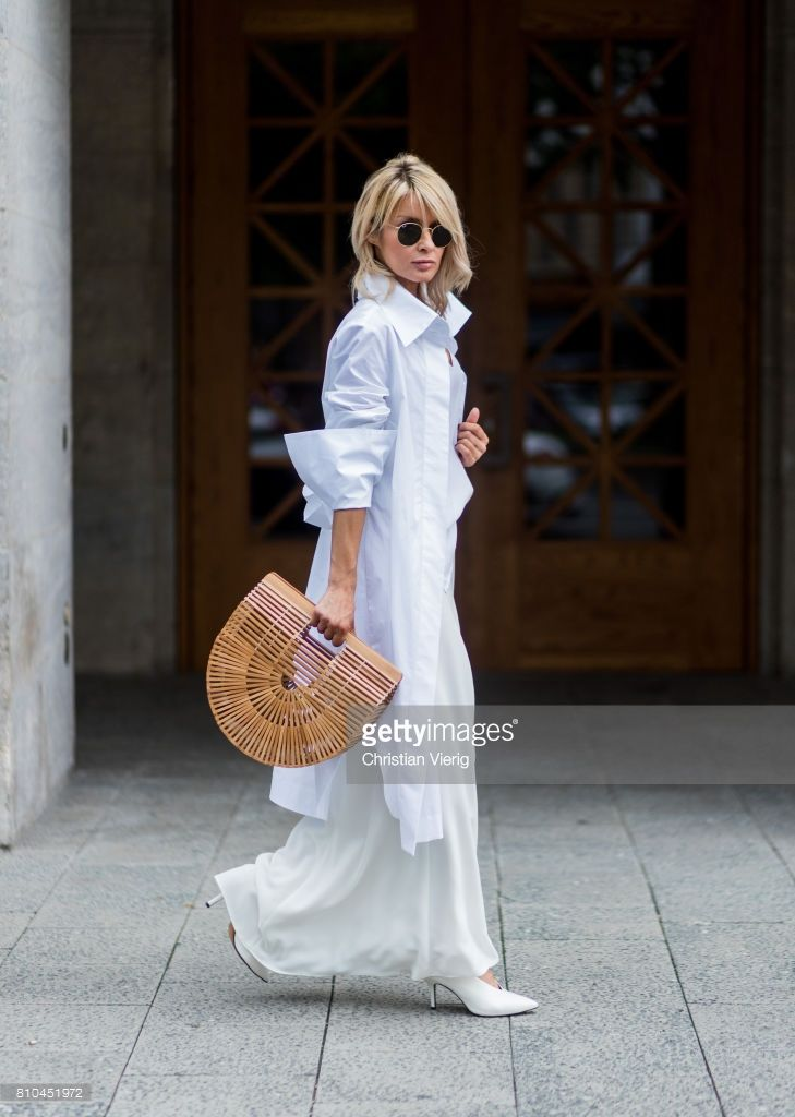 Model and fashion blogger Gitta Banko wearing a white silk top by Jadicted, white oversized blouse by Balossa, a figure-hugging white silk skirt by Furelle, leather pumps with V-cut by Urban Outfitters, a Gaias ark bag by Cult Gaia and sunglasses by Ray B