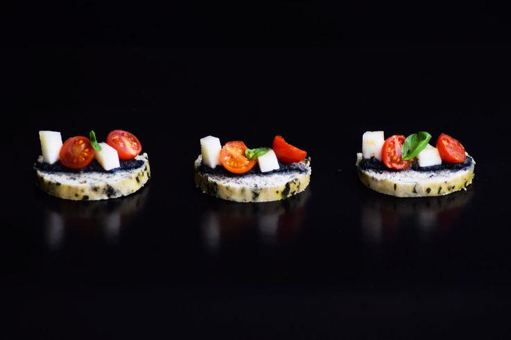 Crostini artesanal de albahaca con puré de aceitunas negras, suave queso de cabra y tomate cherry caramelizado. Próximamente en el catálogo de la línea salada de LIM.