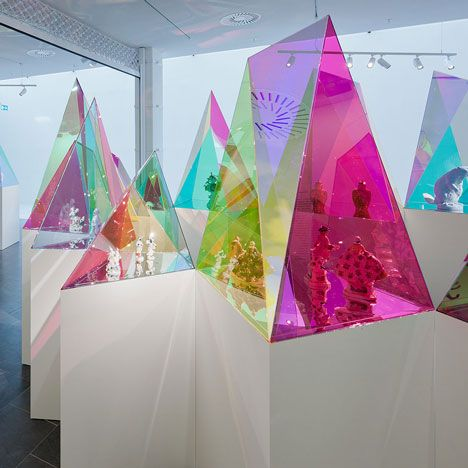 New York architects SO-IL have designed these coloured acrylic display cases in geometric shapes to showcase pieces by German porcelain brand Meissen in an exhibition at Kunsthal KAdE in Amersfoort, the Netherlands.