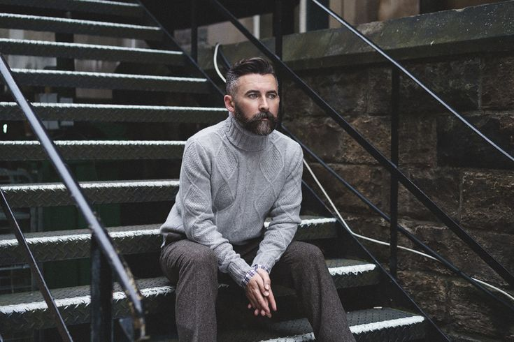 The Modern Gentleman - Tom wears the Ernst roll neck in grey, Ray shirt in navy tartan and Martin trousers in brown fine herringbone.