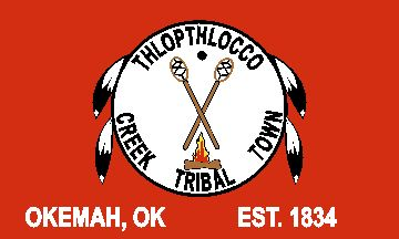 In many ways the flag of the Thlopthlocco Creek reminds the viewer of their cousins the Kialegee. The flag of the Thlopthlocco is dark red and bears a white circle in the center that contains the seal of the Tribal Town. Like the Kialegee, the central element of the Thlopthlocco's seal is a crossed pair of Creek stickball sticks with the basket ends pointing upward. Between the two sticks is a black dot representing the Creek stickball ball.