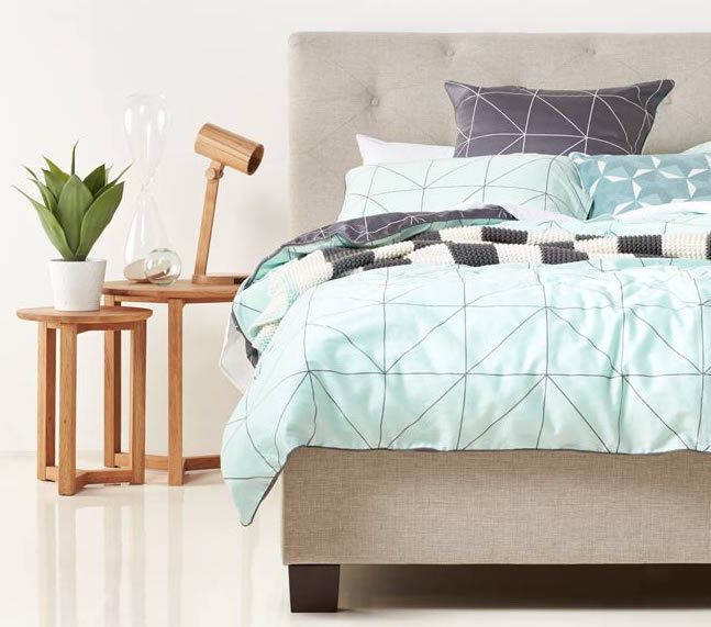 Cool blue linen matched with geometric patterns and wooden side table? Perfection! This Scroll upholstered bed is available exclusively from Bedshed, and the Kami quilt cover set from Aura.