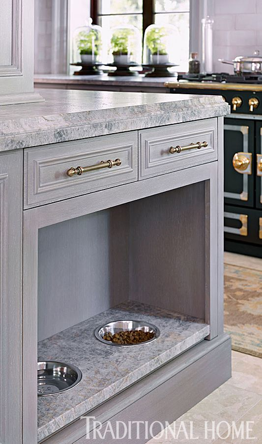 A quartzite slab is tucked in a niche under the island and fitted with drop-in bowls for a stylish pet dining space. - Photo: Emily Jenkins Followill