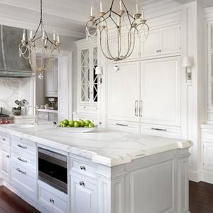Modern French Kitchen with Floor to Ceiling White Kitchen Cabinets, Marble Countertops and Marble Slab Backsplash. White Wood Paneled Double Door Refrigerator with Freezer Drawers.