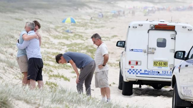 The missing swimmer's friends and family comfort one another as they hunt for him continues at Hawks Nest. Picture: Ryan Osland