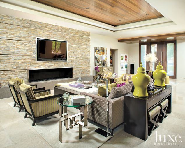 A stacked limestone wall joins a recessed cedar plank ceiling to add texture and warmth