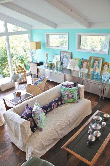 Love the collections in this room - portraits, blue glass, silver on the table.  Love the blue wall, which is a nice pop of color but not overwhelming.  Amazing with the huge windows.