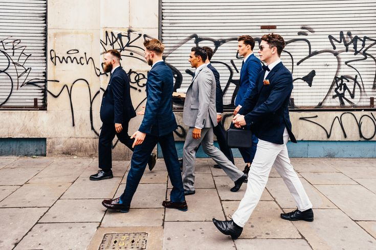 Luke and his groomsmen / ushers walk through the streets of Shoreditch, London  On the blog: creative urban wedding photography at Village Underground warehouse wedding venue in London by alternative wedding photographer Babb Photo.   www.babbphoto.com