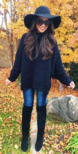 schwarzer pullover mit blauen jeans und schwarzen kniehohen stiefeln