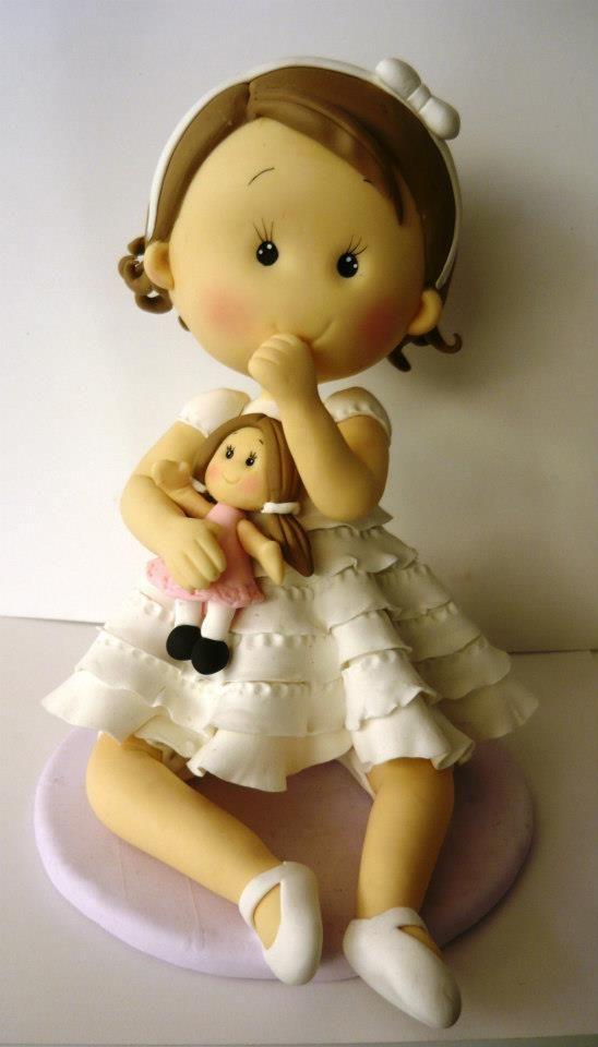 Niña con vestido blanco y muñeca.
