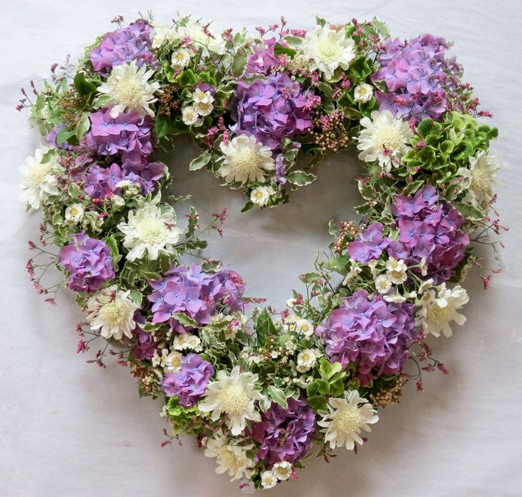 Heart shape with white and coral/light orange flowers and greens