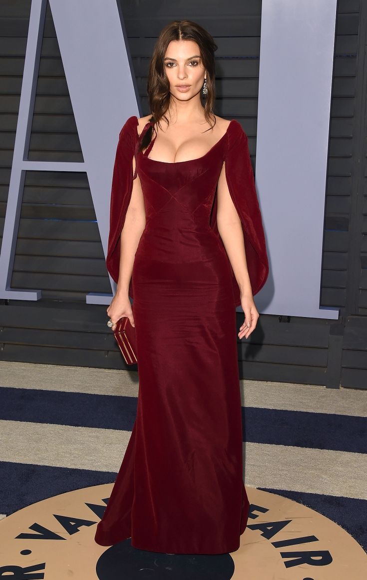 EMILY RATAJKOWSKI  wears a scoop-neck maroon Zac Posen gown with attached cape, matching clutchand her new wedding ringtotheVanity Fairparty.
