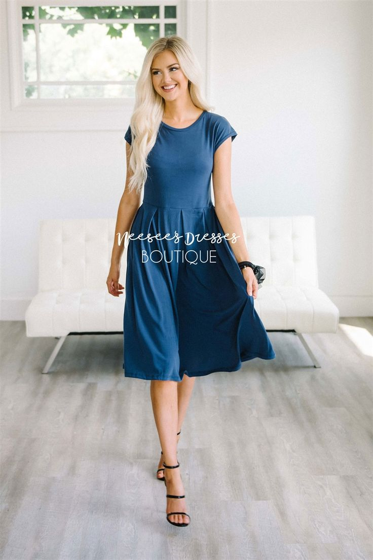 Every woman needs a beautiful go-to, solid dress! This soft and flattering dress is just the one. Navy dress features a round neckline, short rolled sleeves and a pleated waist.