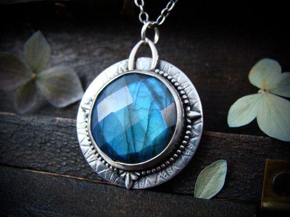 Este misterioso labradorita ilumina de color azul brillante impresionante desde todos los ángulos. La piedra ha sido decorada con delicado compás como detalles. La base de la botonera ha sido rodillo impreso con un diseño radiante. La plata ha sido oxidada para añadir dramatismo y contraste. La parte trasera tiene una ventana circular para que la luz brille a través de la piedra.  ☞ Tamaño ~ 1 1/4 x 1  cadena de 18 con labradorita acento. Bisutería fácil.  Lore de gema ☞ ~ labradorita es…